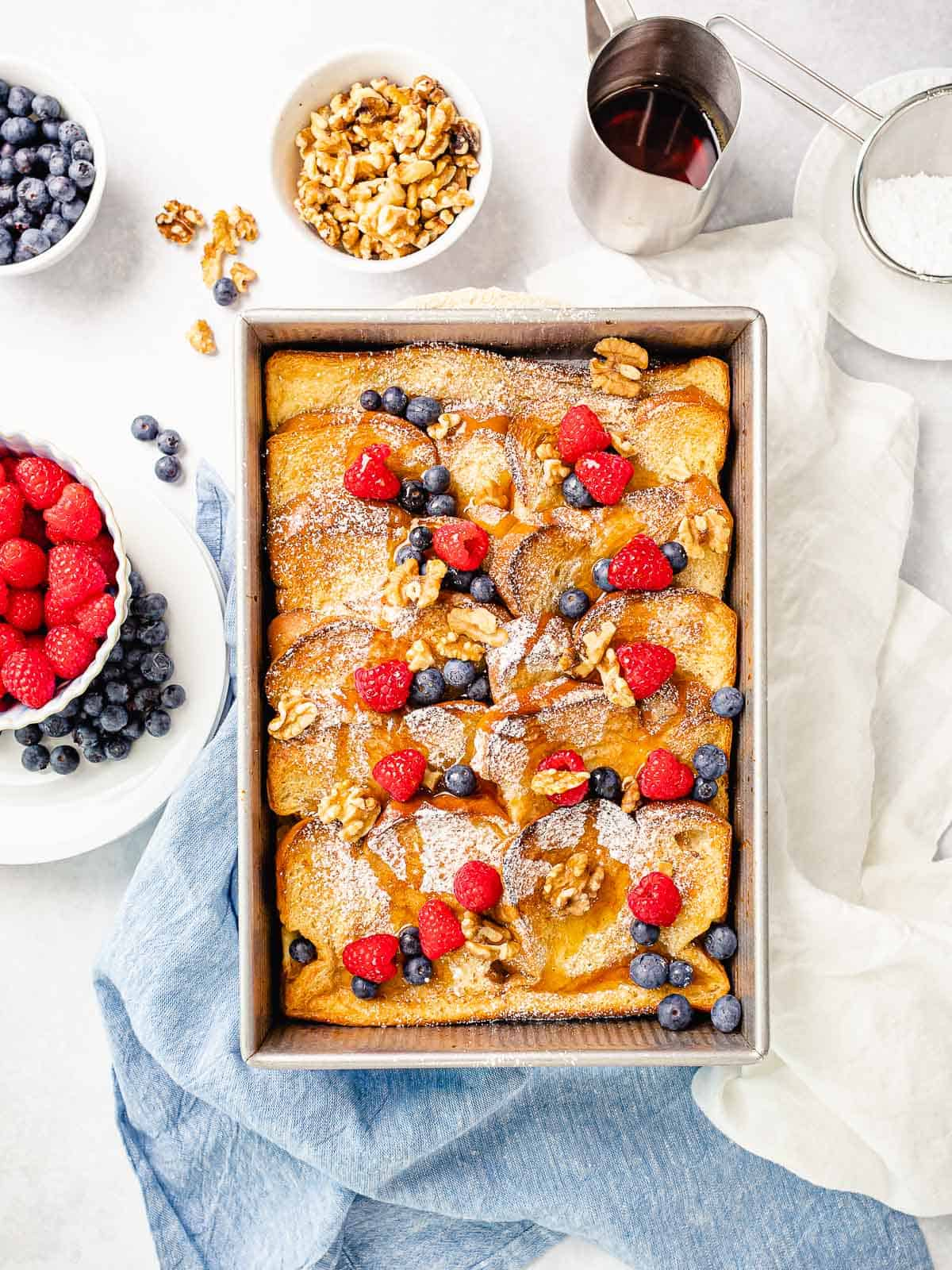 Overnight baked french toast casserole with blueberries, rapsberries, and maple syrup surrounded by toppings.