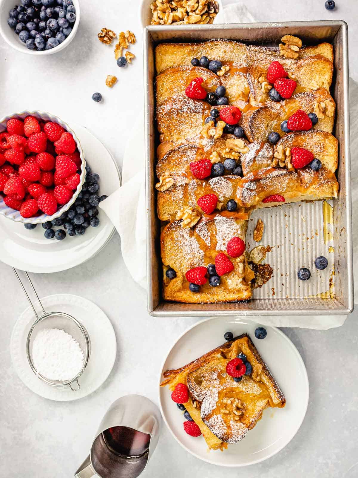 Baked french toast in a baking pan with golden brown crispy crust topped with blueberries, raspberries, nuts, and maple syrup.