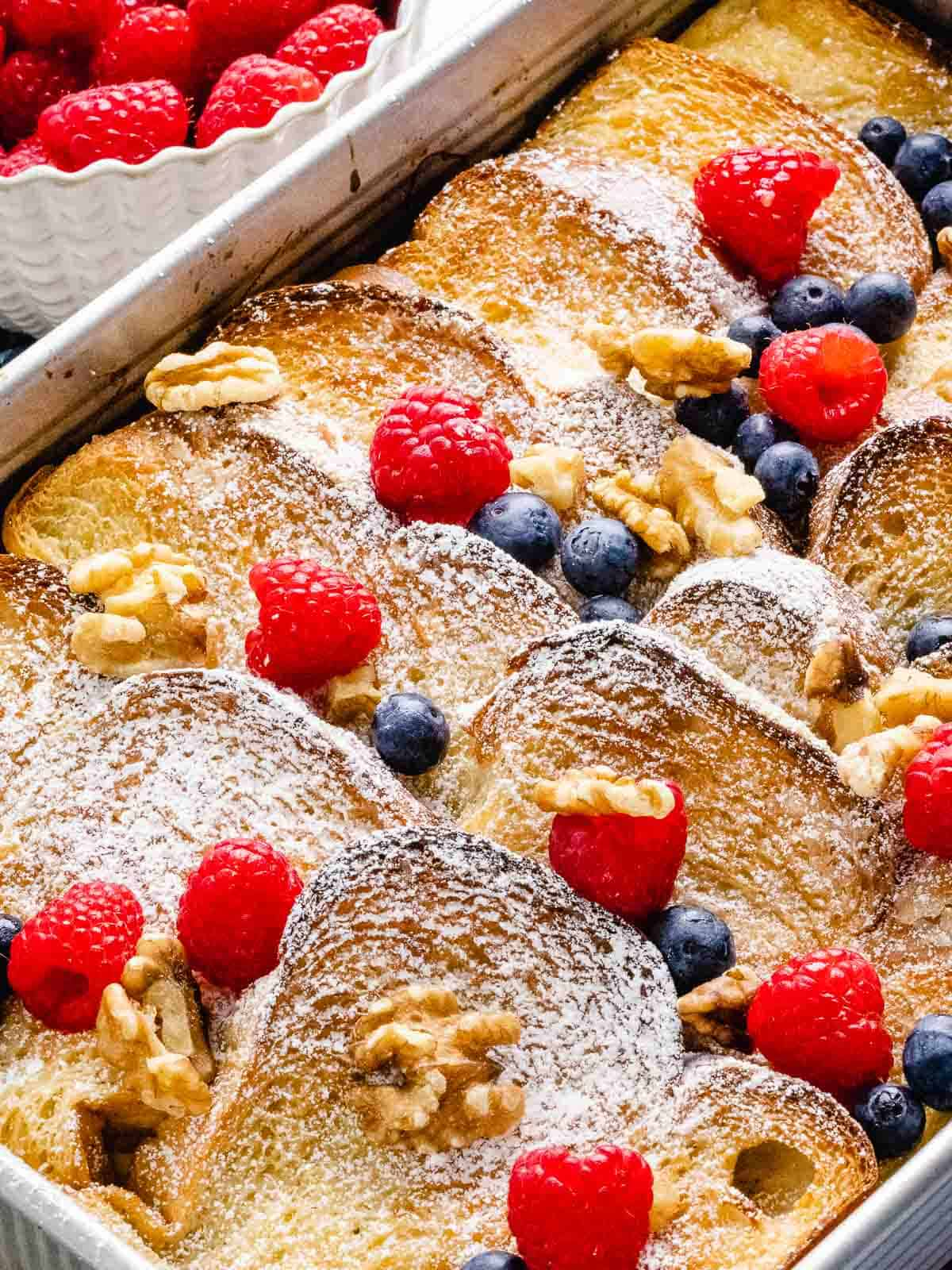 Overhead of french toast casserole in a baking pan topped with blueberries, raspberries, and walnuts dusted with powdered sugar.