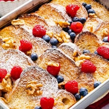 Baked French Toast Casserole with crunchy golden brown crust topped with berries and nuts.