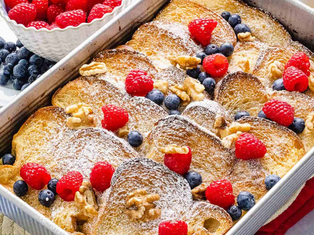Baked french toast casserole with cinnamon, blueberries, raspberries in a baking dish.