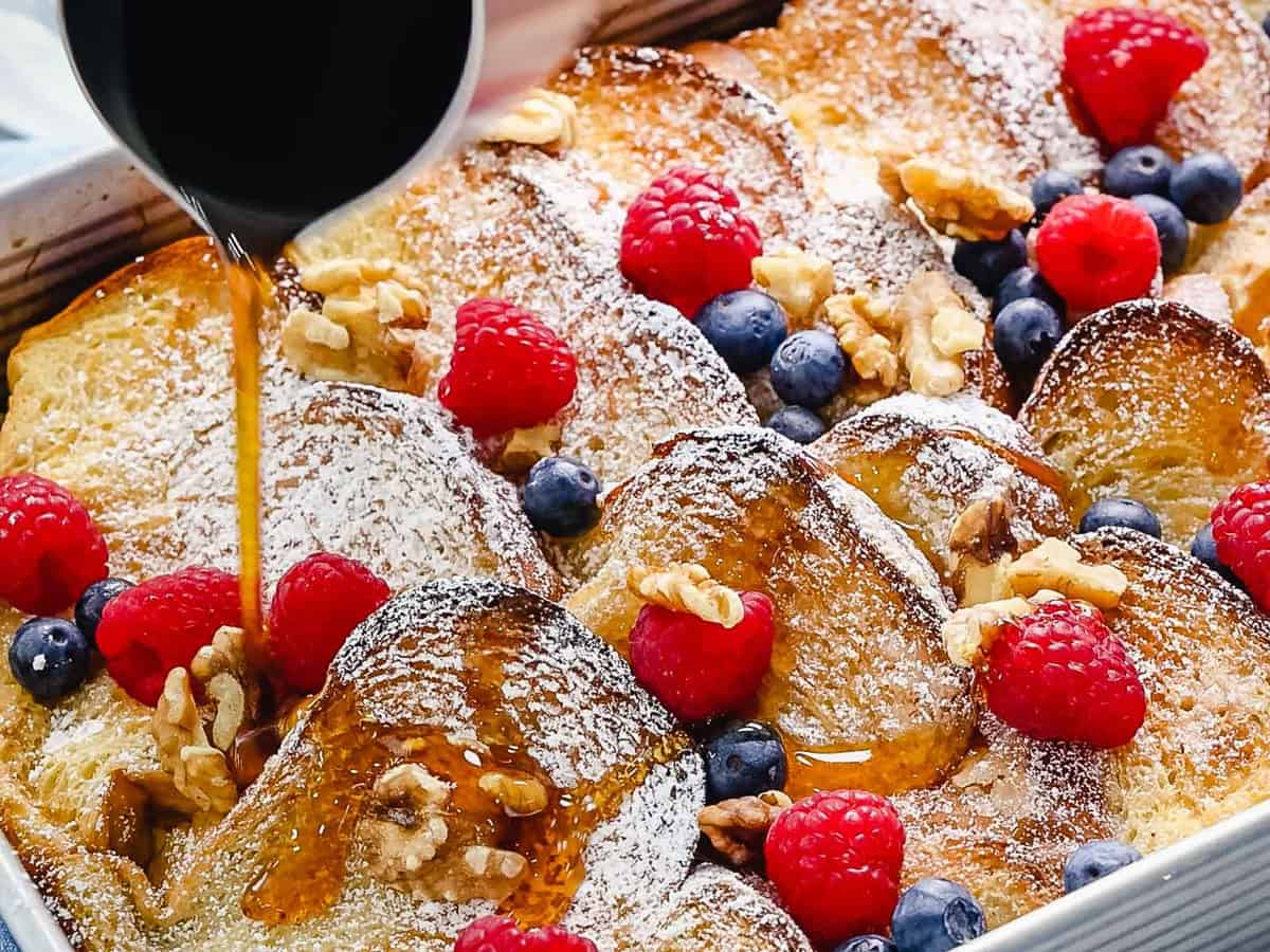Overnight baked French toast with a golden brown crunchy topping drizzled with maple syrup and topped with fruit.