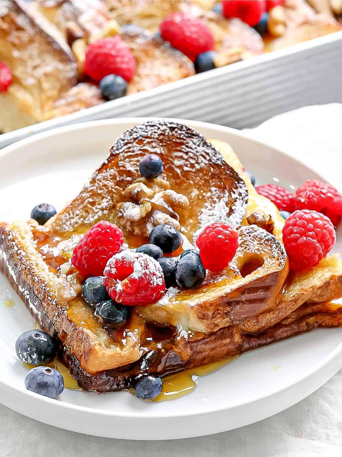 Slice of baked french toast with blueberries, raspberries and powdered sugar on a white plate.
