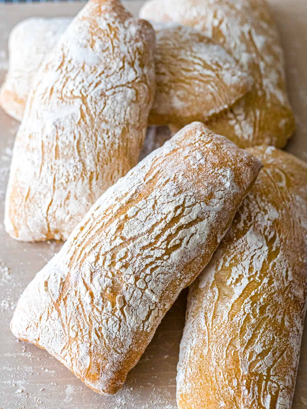Several ciabatta bread loaves with a golden brown, crispy crust covered in flour.