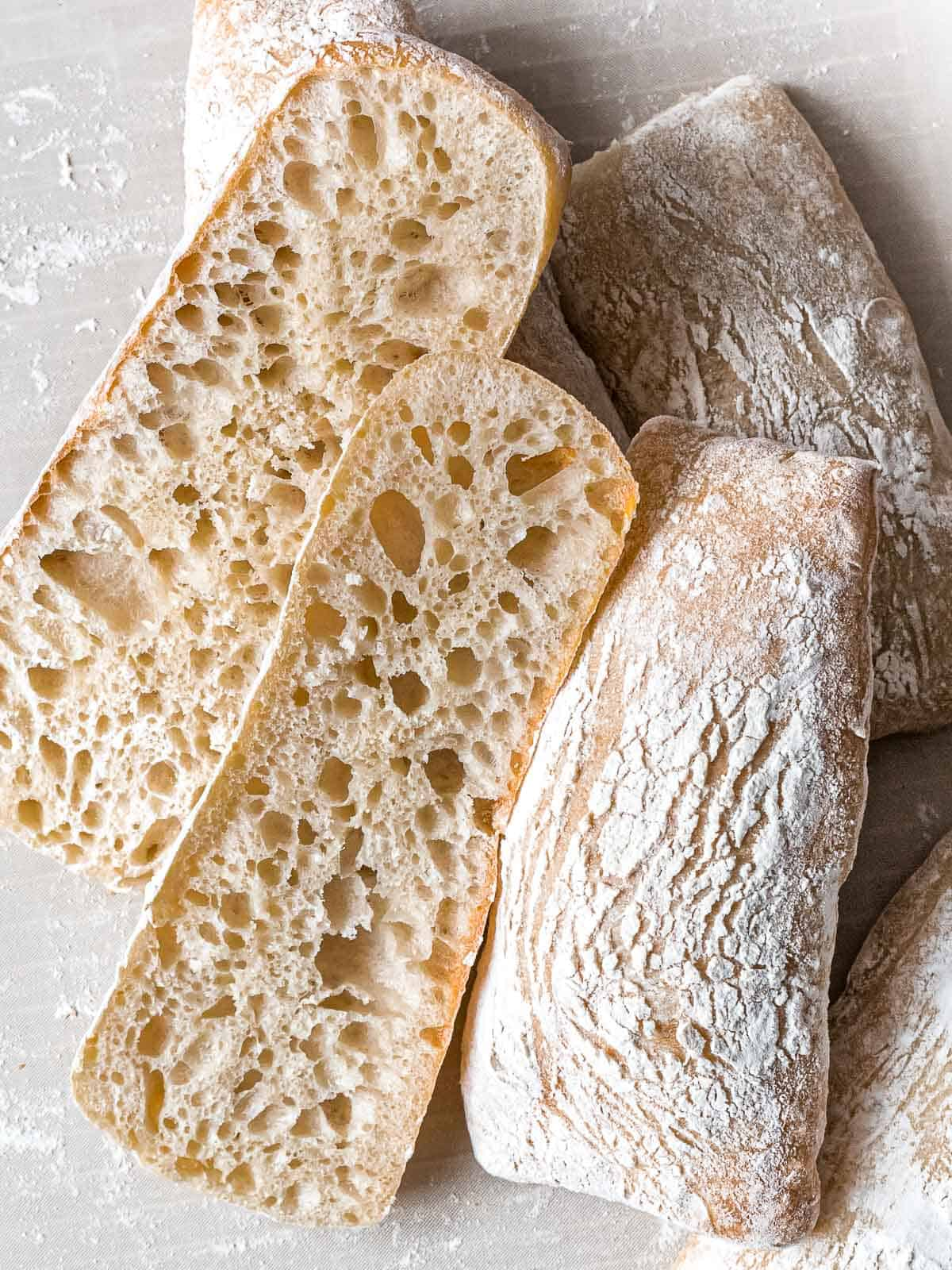 Sourdough ciabatta sliced open with large holes to show open crumb and proper gluten development laying in a pile of more loaves.