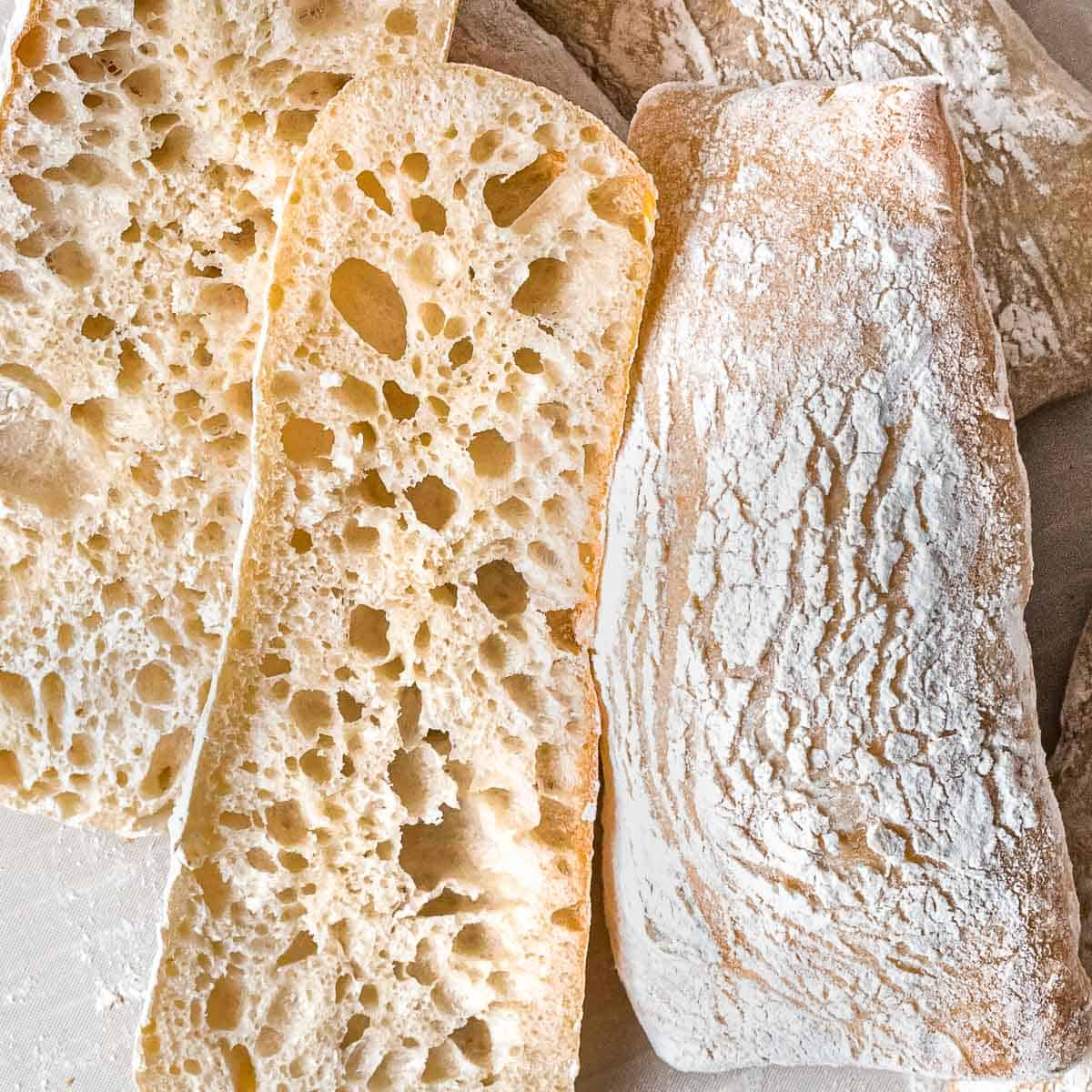 Sourdough ciabatta cut open to reveal large holes to show an open crumb with a crisp, crackly crust.