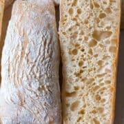 Sourdough ciabatta bread cut open to reveal large, irregular holes with a thin, crispy crust.