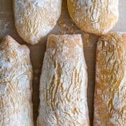 Baked ciabatta loaves with a golden crispy crust covered with flour.