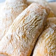 A pile of sourdough ciabatta loaves baked with a golden crust covered with flour.