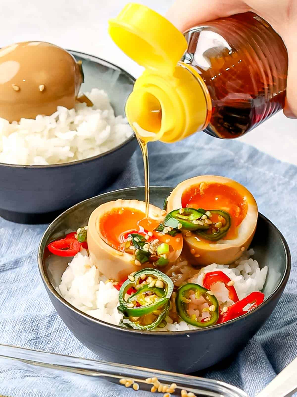 Sesame oil drizzled on top of a mayak egg cut in half placed on top of rice and garnished with peppers.