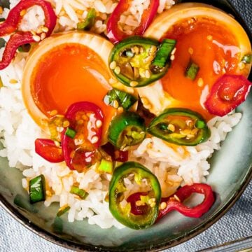 Mayak egg cut in half with marinade of red and green chilis on top of white rice.