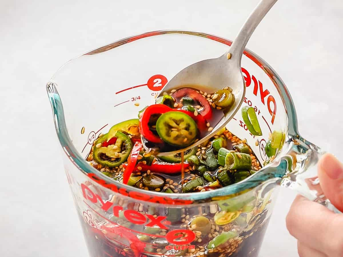 Mayak egg marinade of soy sauce, red and green peppers, scallions in a glass pyrex bowl.