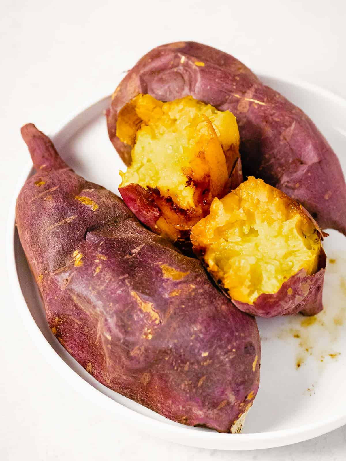 Baked Korean sweet potatoes also called gungoguma 군고구마 on a white plate.