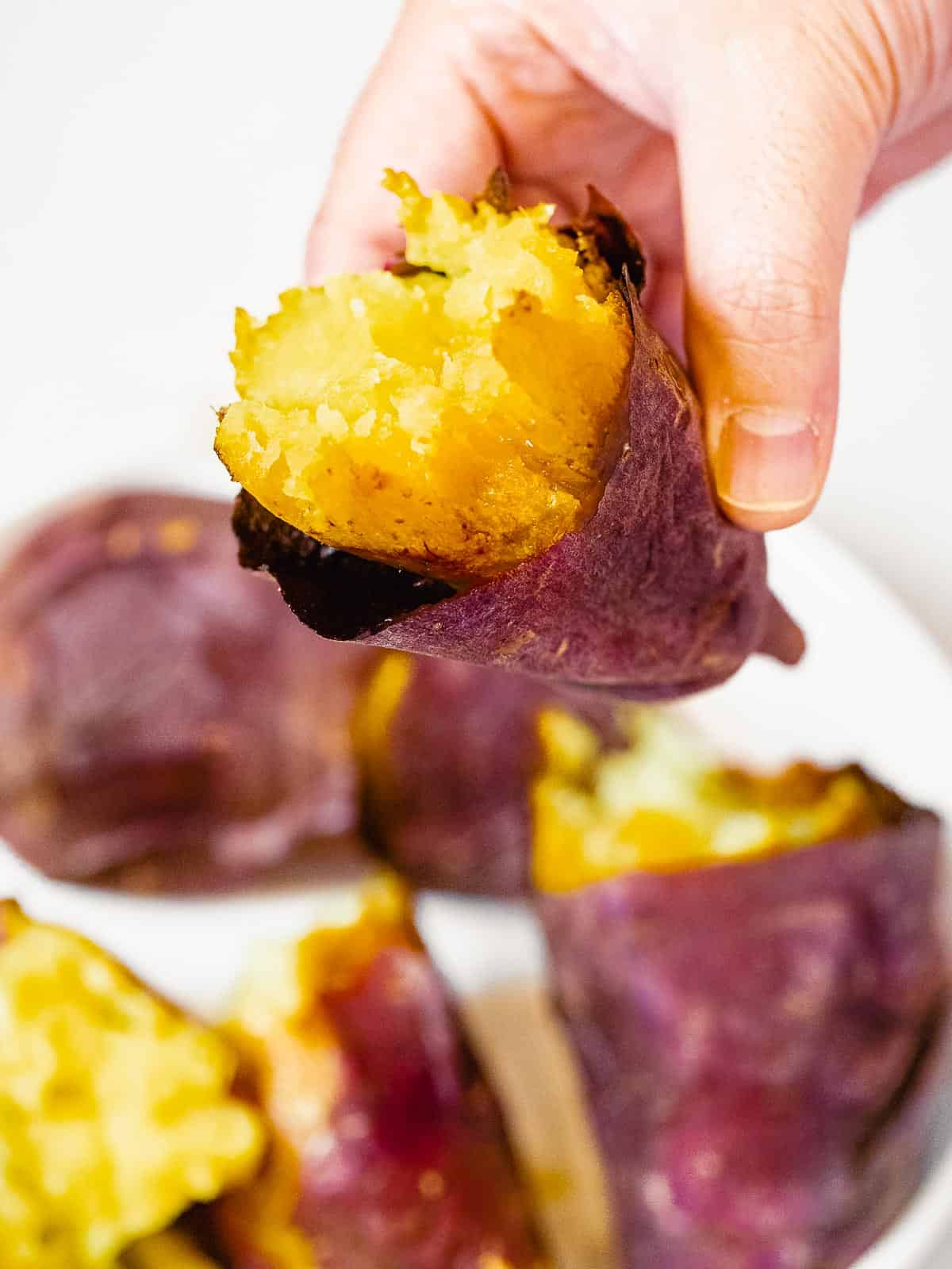 Hand holding a roasted Korean sweet potato baked until soft and fluffy.