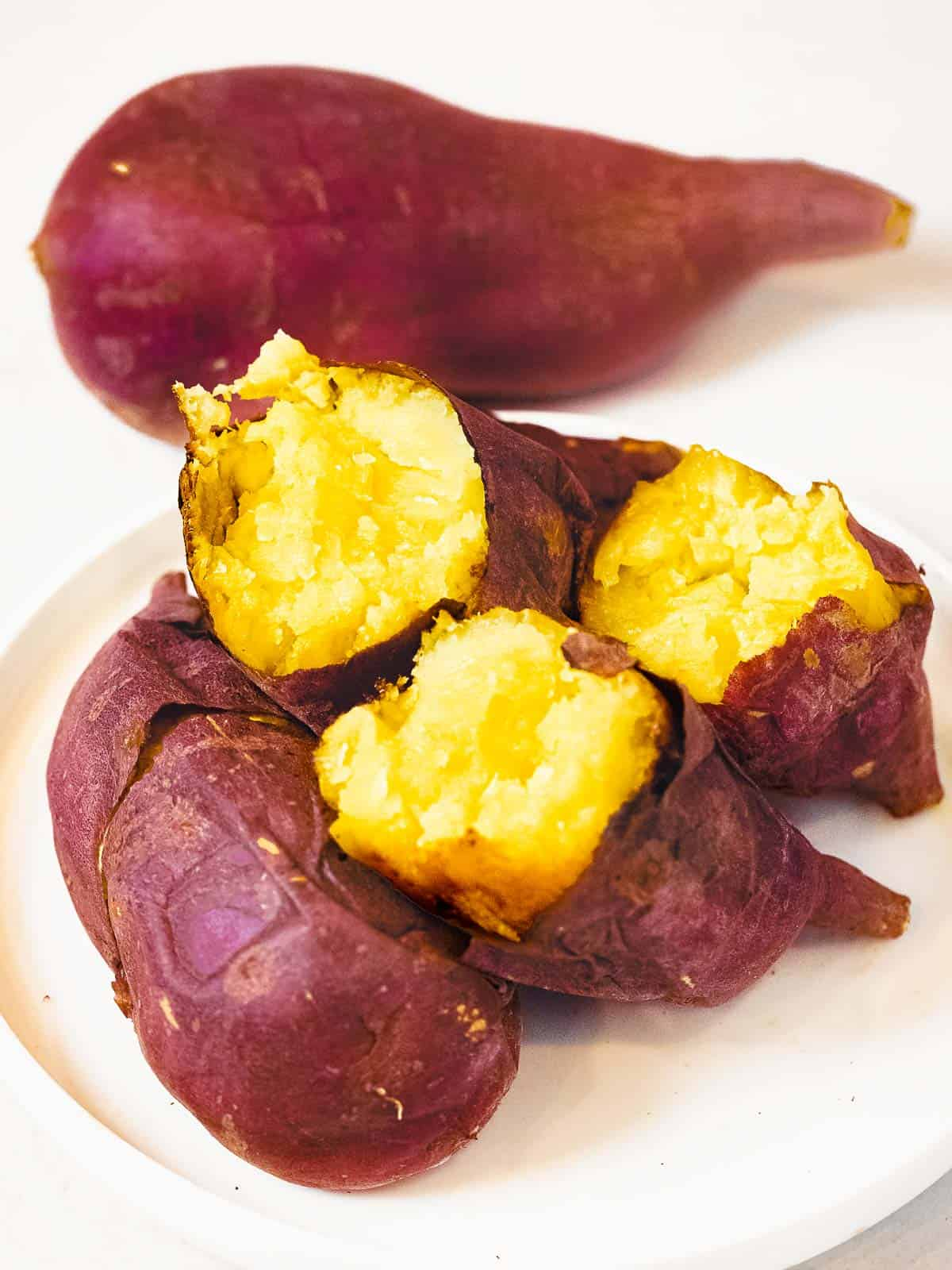Korean sweet potatoes baked in the oven until soft and fluffy split open to reveal golden yellow flesh with crispy purple skin.