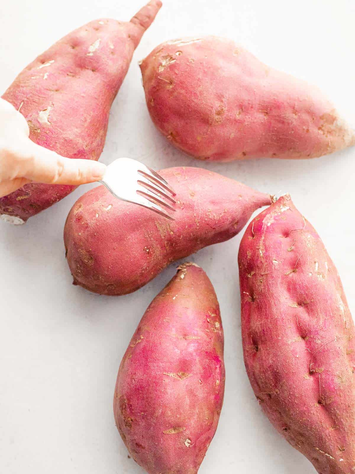Korean sweet potatoes being poked with a fork before roasting.