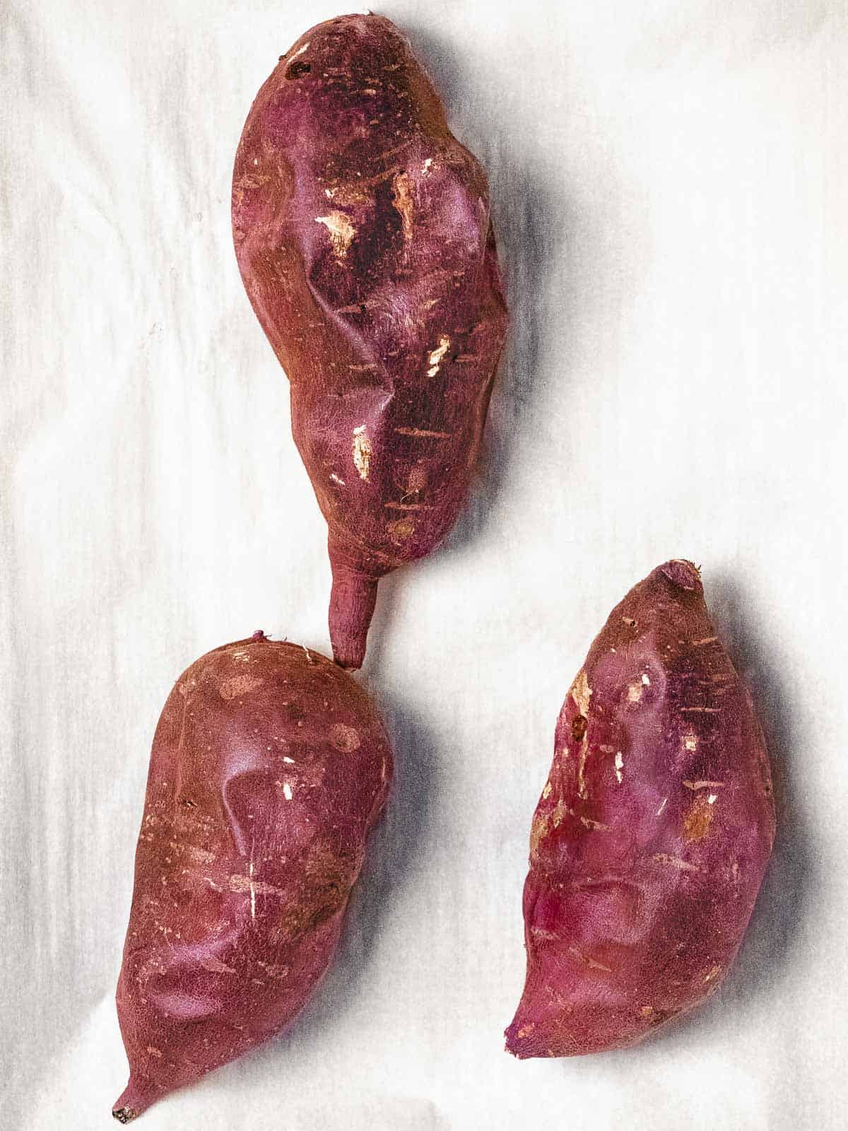 Roasted Korean sweet potatoes (Gungoguma 군고구마) with wrinkled purple skin.