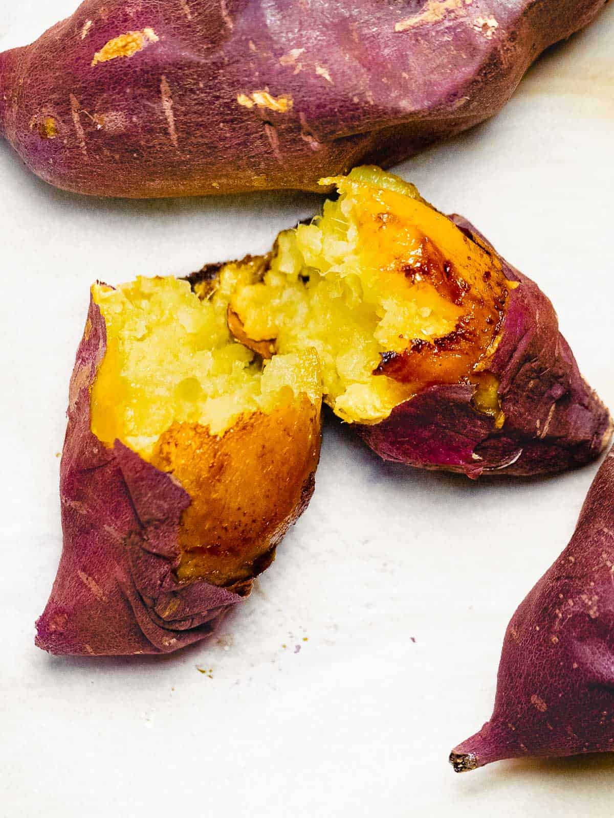 Korean sweet potato baked until golden brown and caramelized split in half to reveal golden yellow color inside.