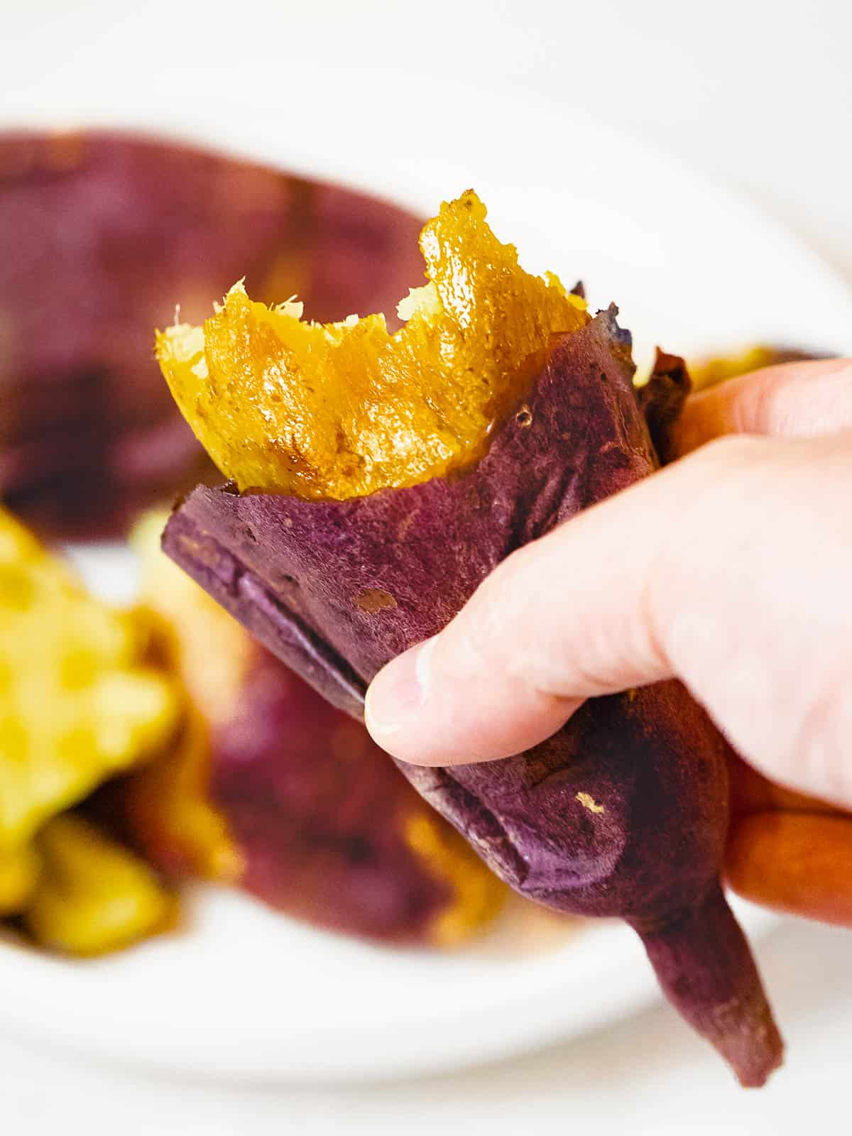 Hand holding a perfectly baked Korean sweet potato with golden, caramelized inside and crisp purple skin.