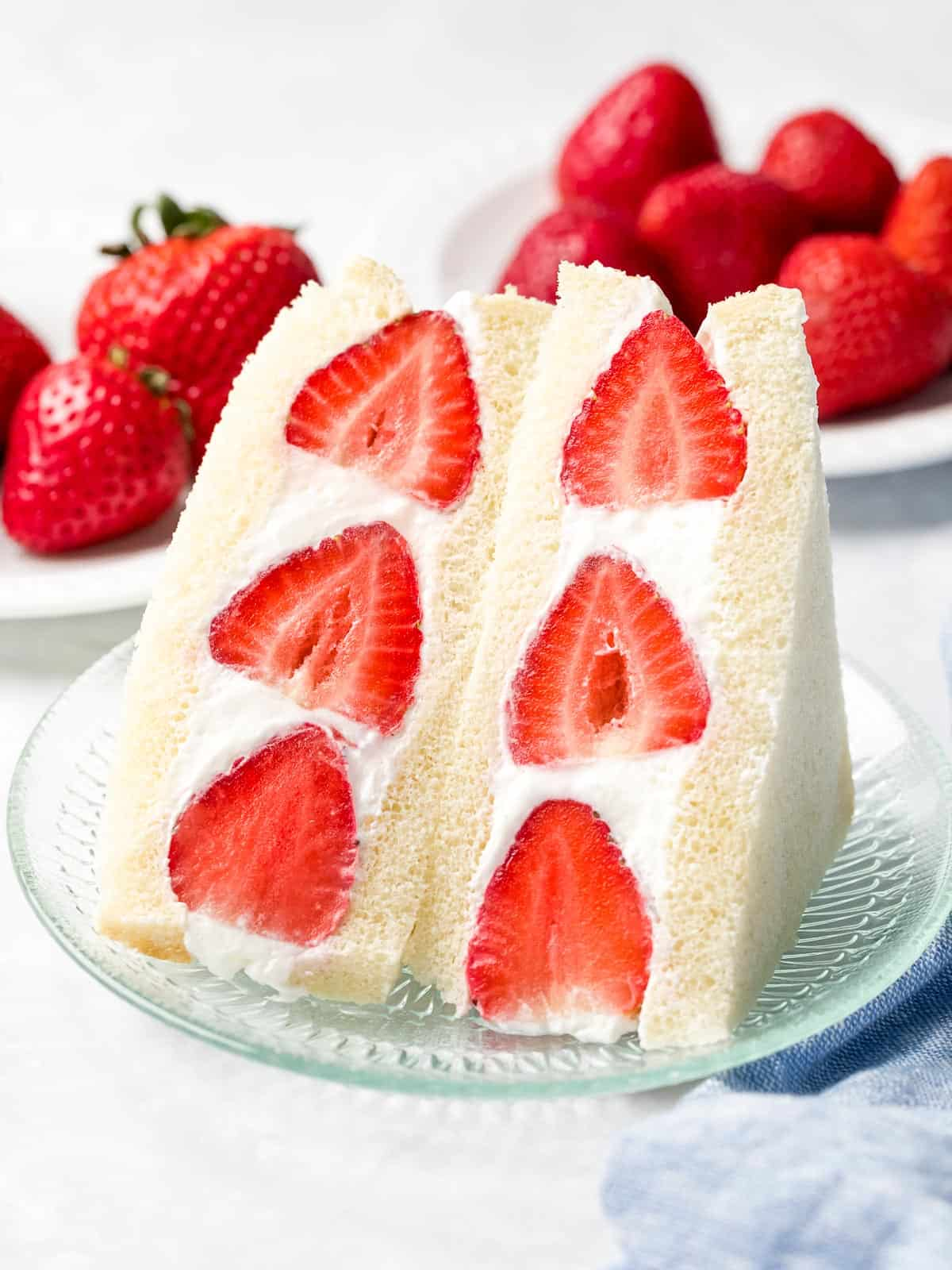 Japanese fruit sando made with strawberries and whipped cream sliced in half next to a plate of red strawberries.