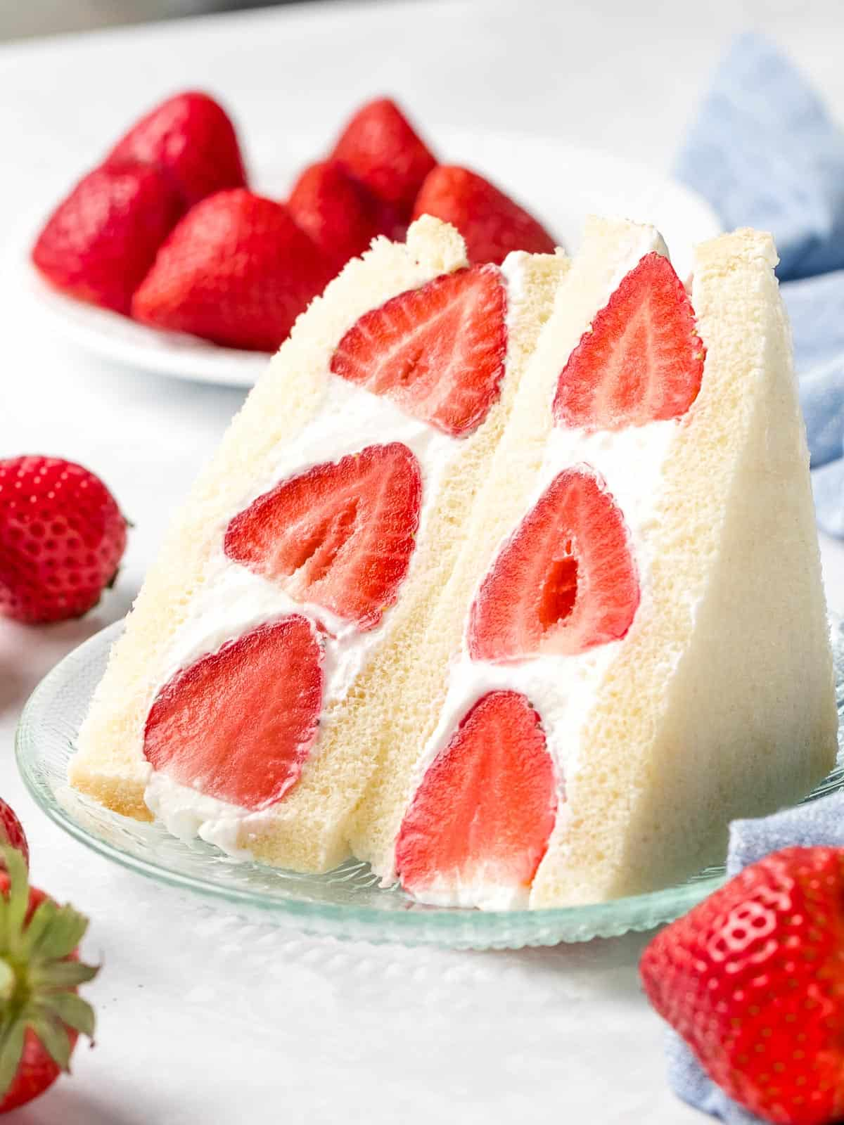 Japanese strawberry fruit sando made with soft milk bread and fluffy whipped cream sliced in half.