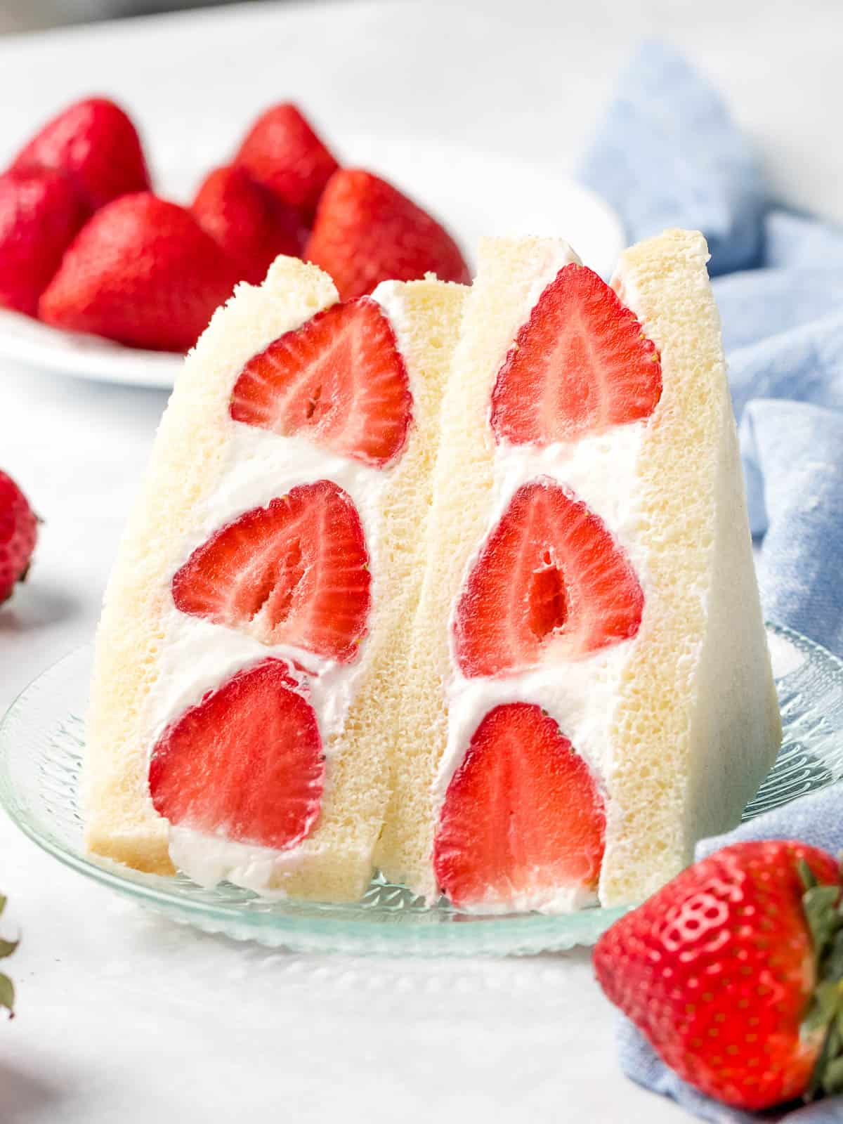 Japanese strawberry sando made with red strawberries and whipped cream sliced in half next to a plate of strawberries.