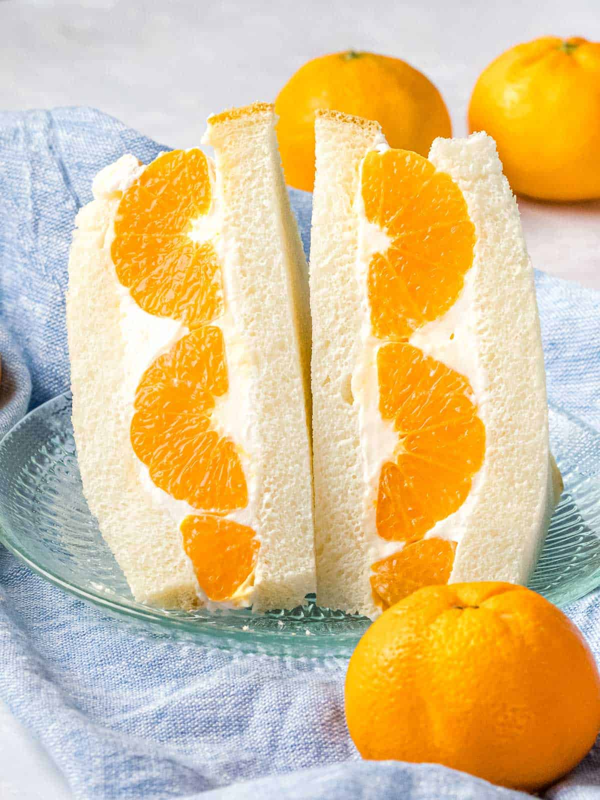 Japanese fruit sando made with mandarin oranges that's sliced in half on a glass plate.
