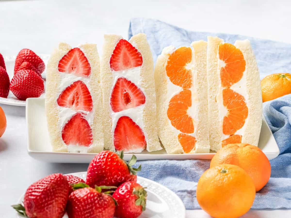 Japanese fruit sandwich made with strawberries and mandarin oranges filled with whipped cream and sliced in half.