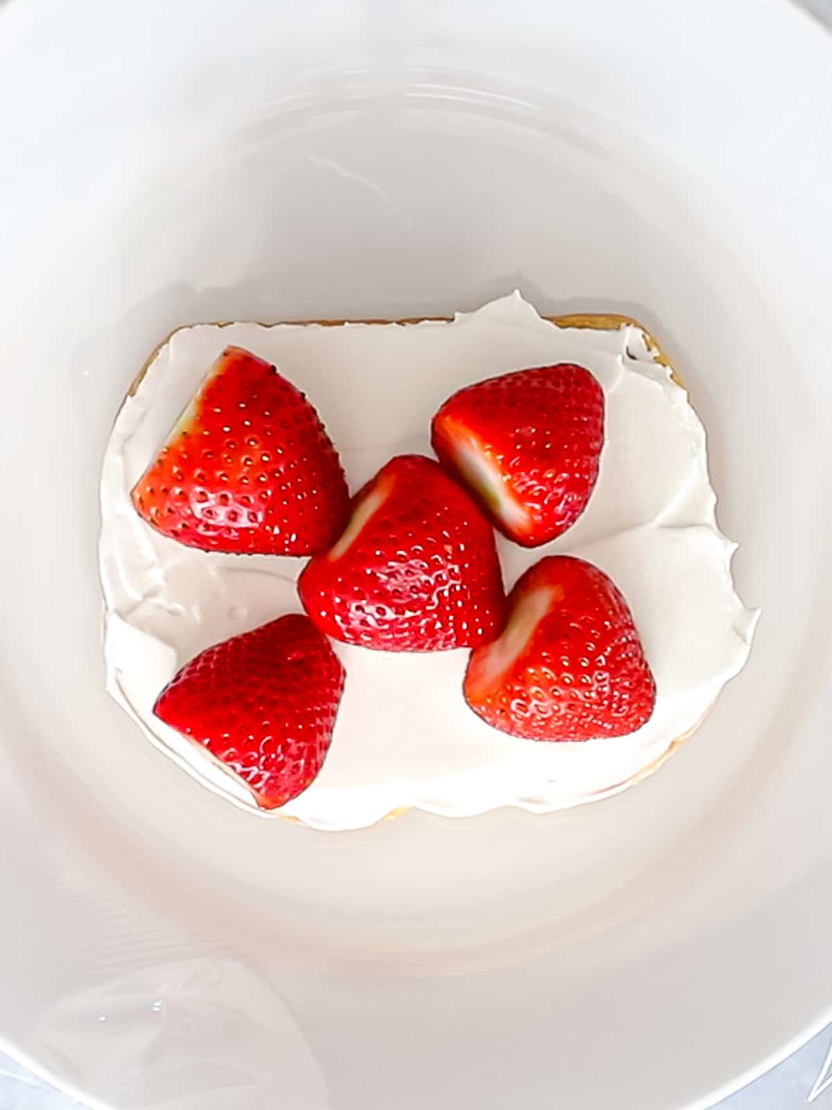 Red strawberries laid on top of whipped cream and Japanese shokupan or milk bread.