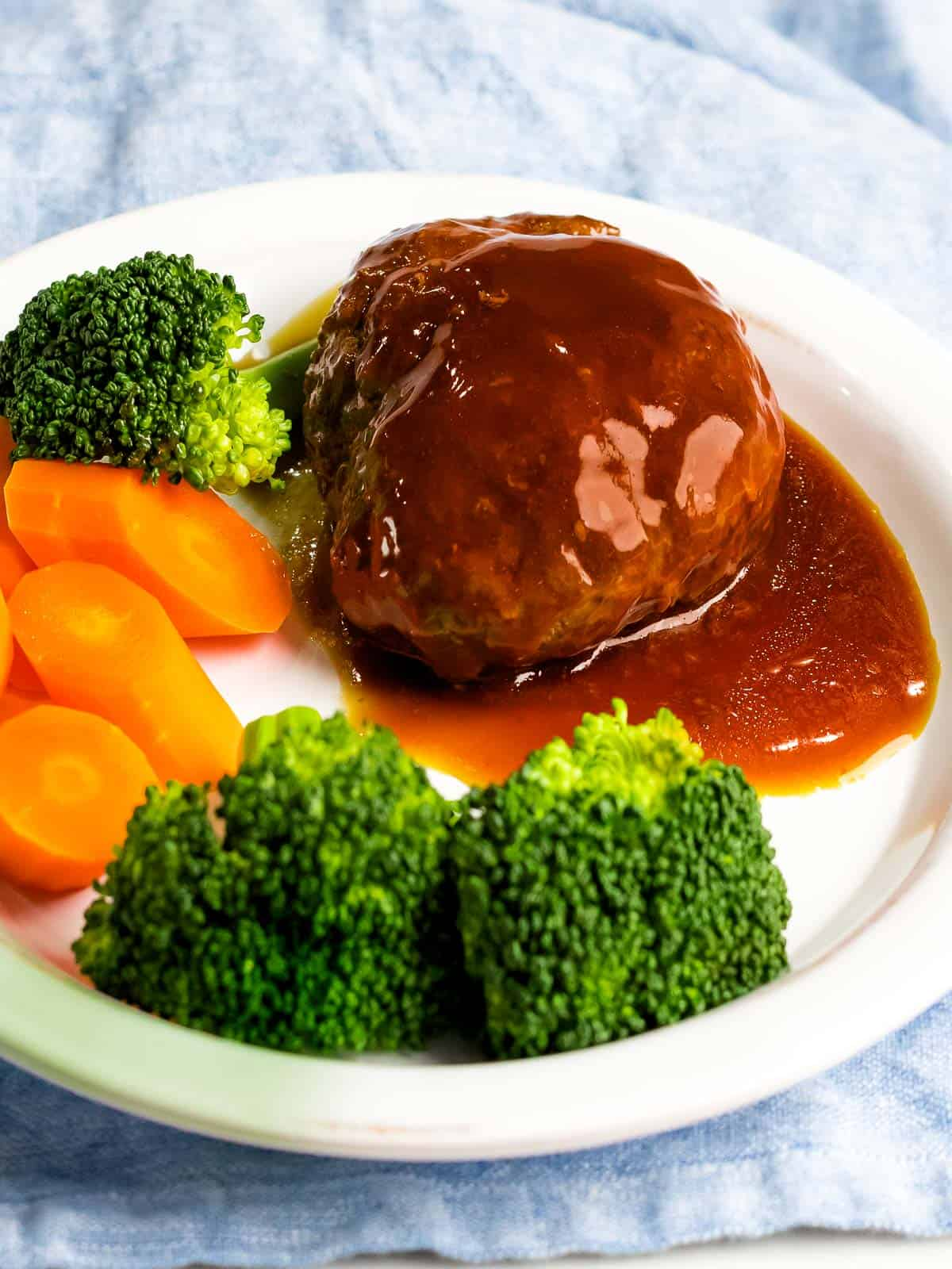 Juicy, tender Japanese hamburger steak (hambāgu ハンバーグ) covered in tangy gravy on a white plate next to carrots and broccoli.