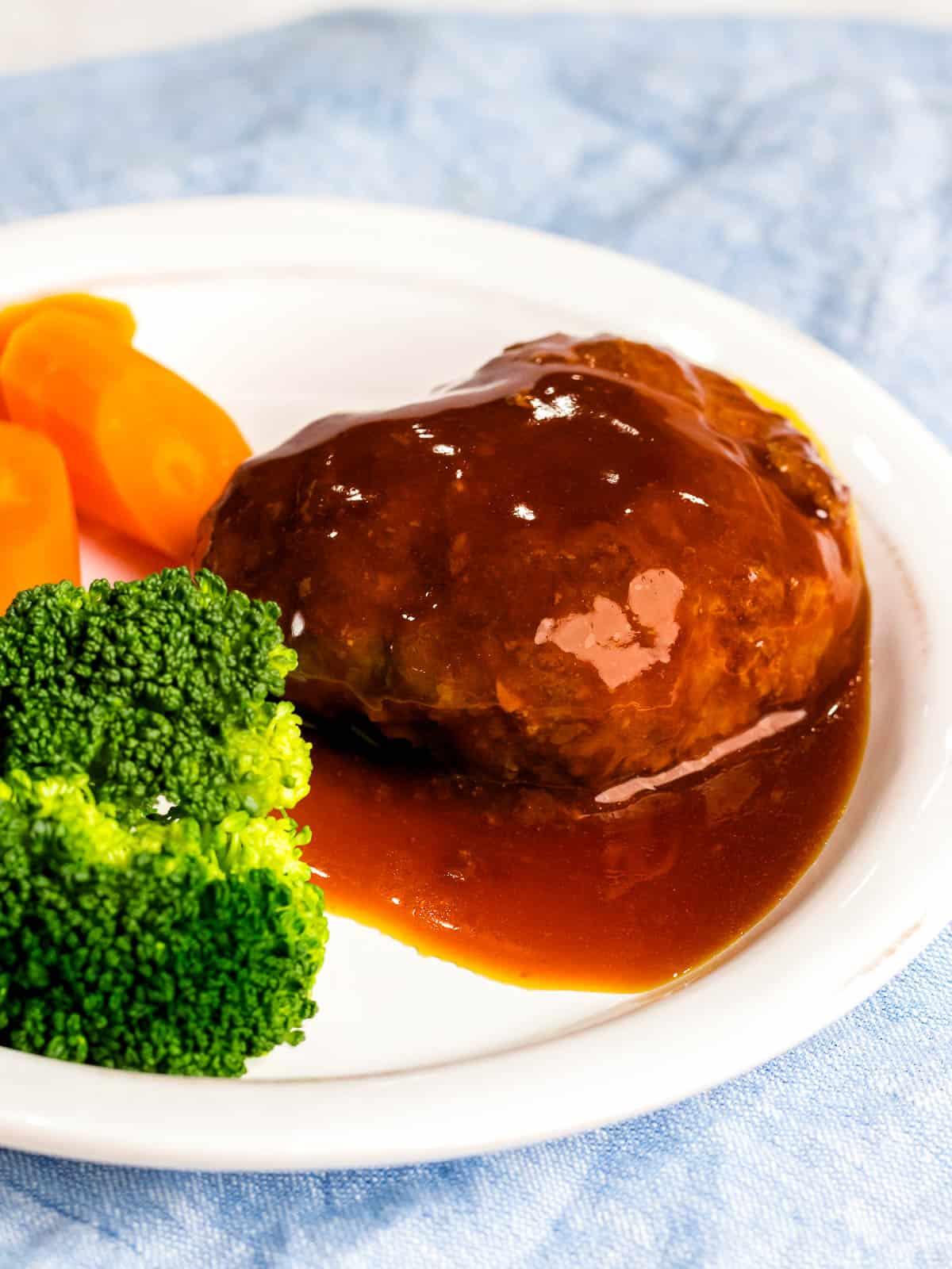 Juicy Japanese hamburger steak (hambāgu ハンバーグ) covered in sauce on a white plate next to carrots and broccoli.