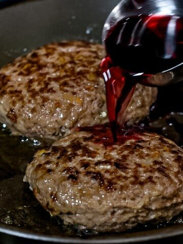 Red wine being added to Japanese hamburger steaks cooking in a pan.