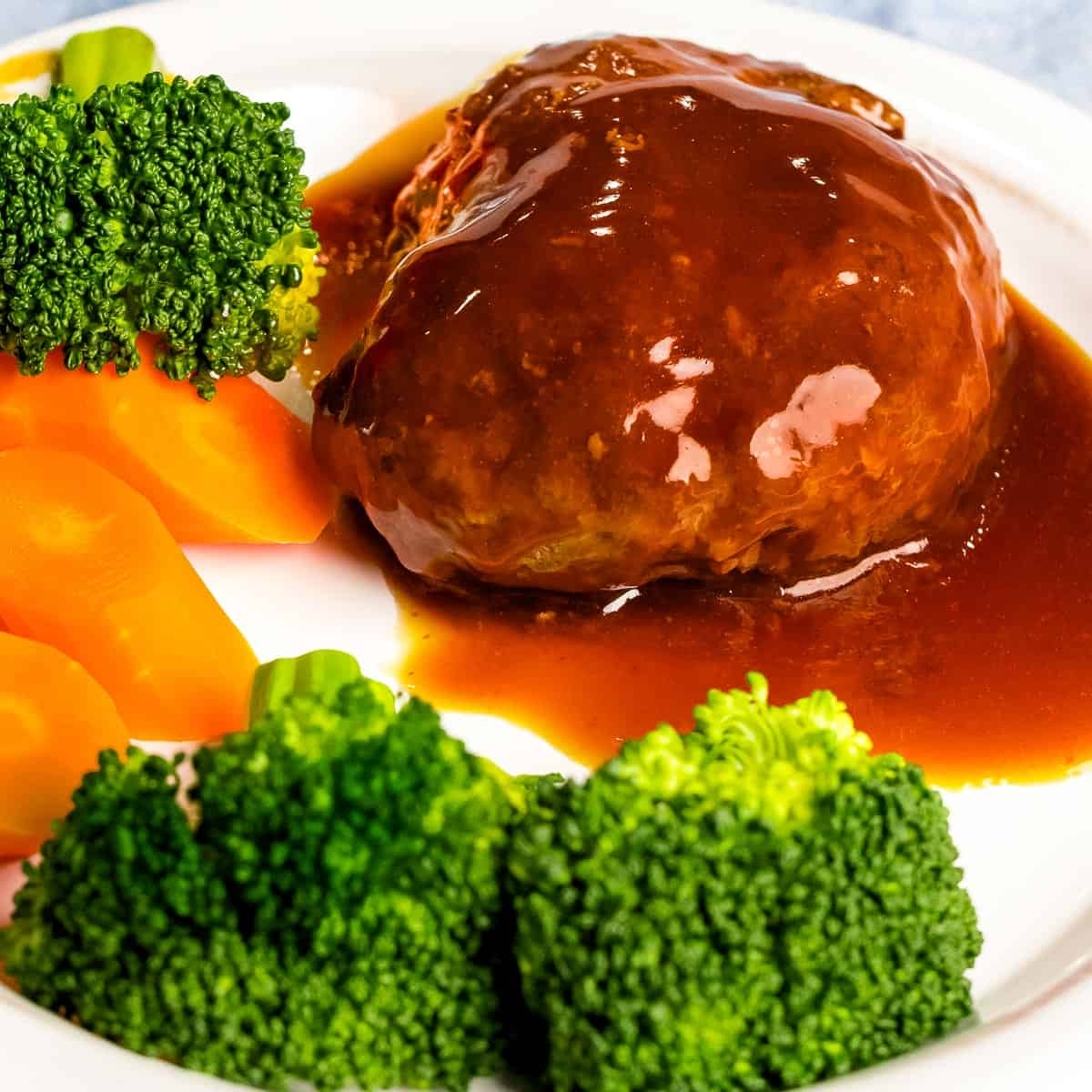 Japanese hamburger steak (hambāgu ハンバーグ) on a white plate next to broccoli and carrots.