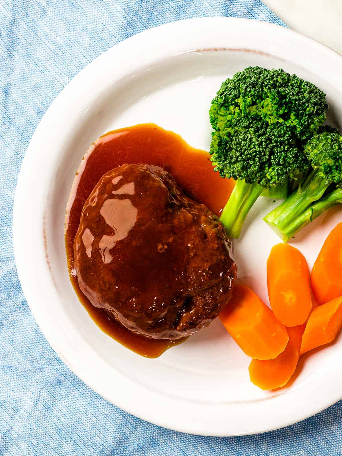 Japanese hamburger steak (hambāgu ハンバーグ) covered in tangy brown gravy on a white plate next to carrots and broccoli.