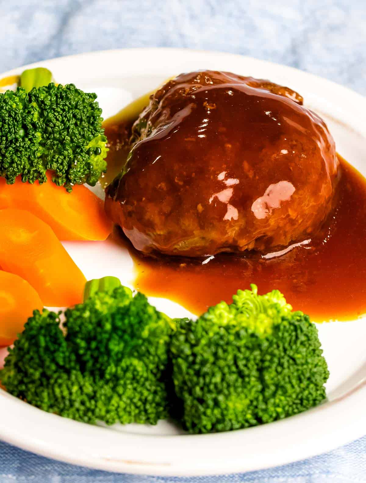 Juicy, tender Japanese hamburger steak (hambāgu ハンバーグ) covered in tangy brown gravy on a white plate next to carrots and broccoli.