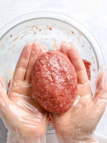 Hambagu patty of ground meat formed into a round oval shape and held in hands.
