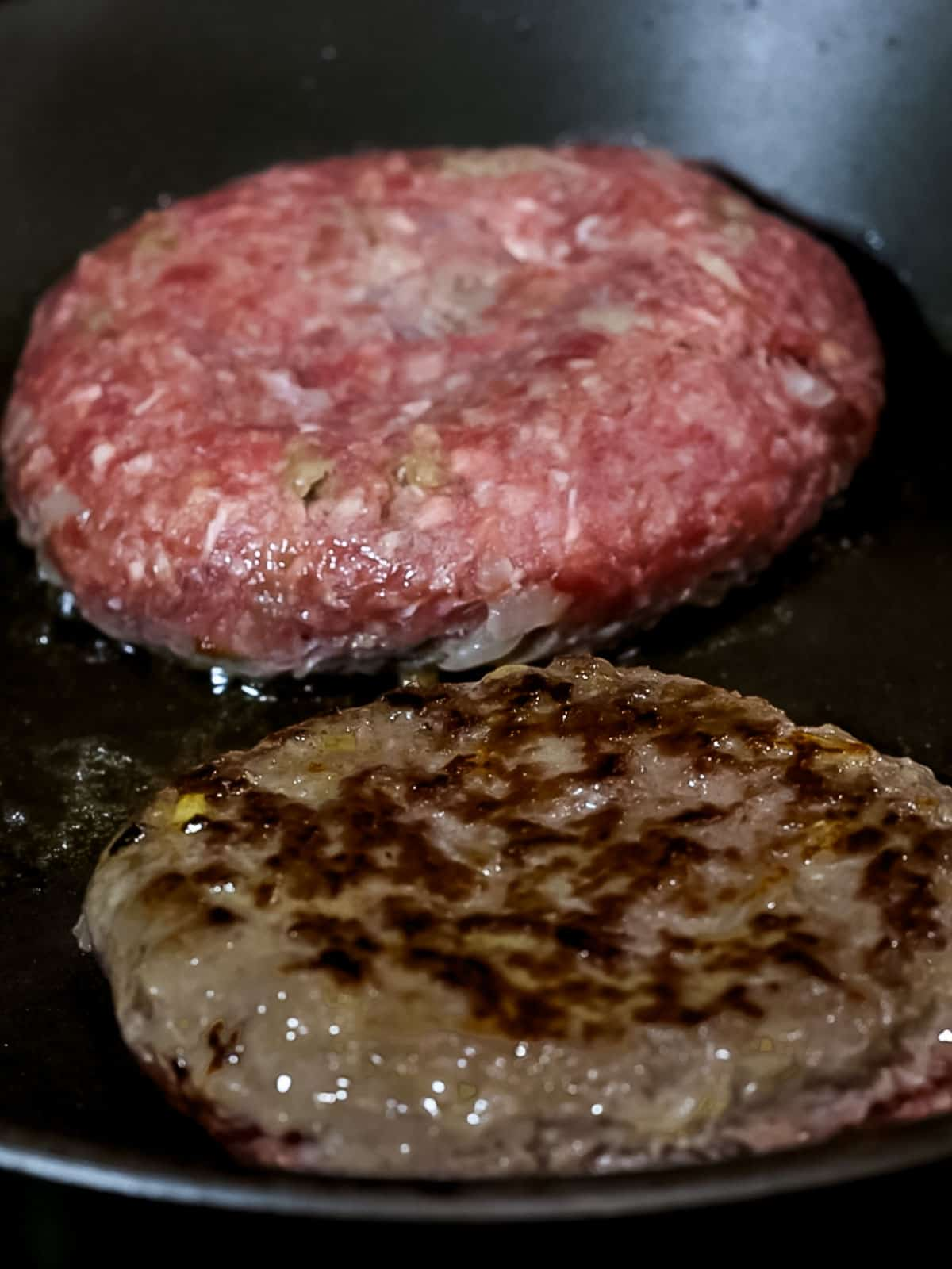 Japanese hamburger steak patties cooking in a pan with golden brown edges.