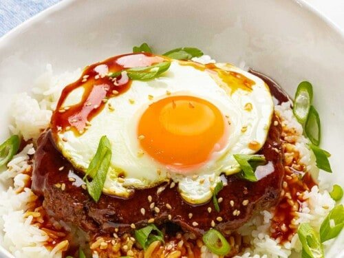 Hawaiian loco moco with a burger, gravy, white rice, and a sunny side up egg in a white bowl.