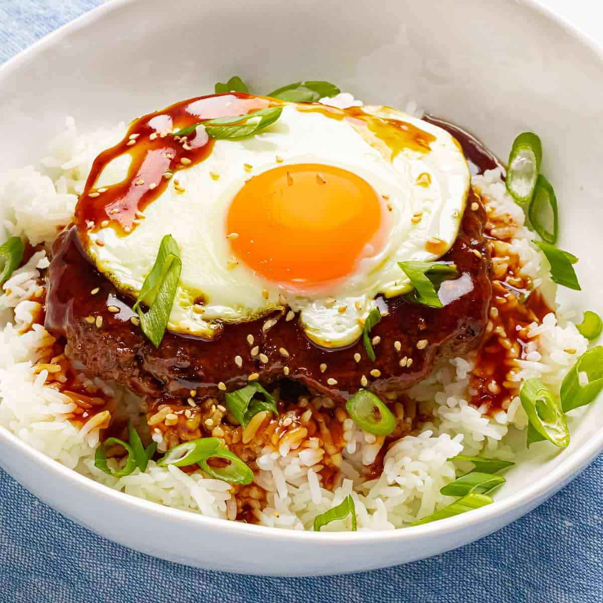 Loco moco made with a juicy beef burger patty on top of rice with brown gravy and a sunny side up egg.