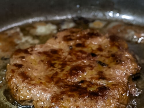 Loco moco beef burger patty cooked to golden brown in a frying pan.