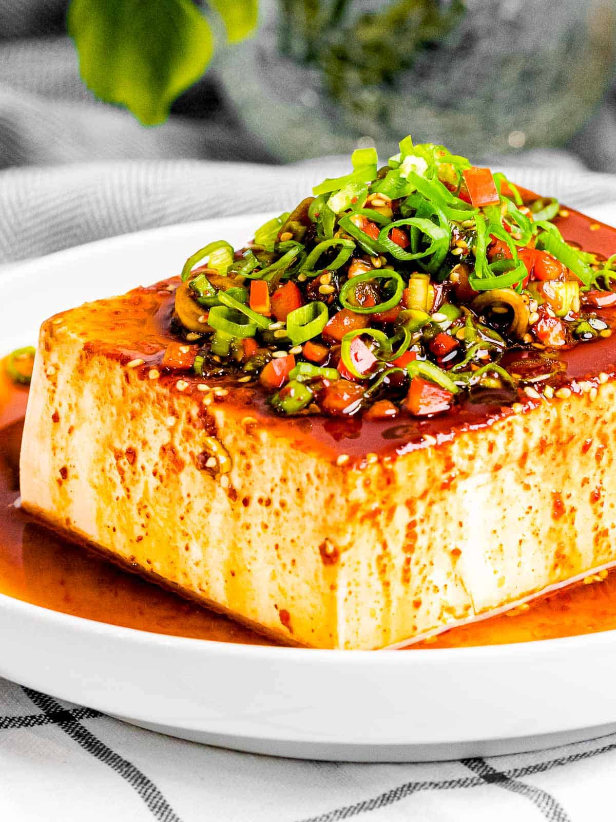Silken tofu with Korean soy sauce made of green onions, peppers, sesame oil, and red pepper flakes in a white bowl.