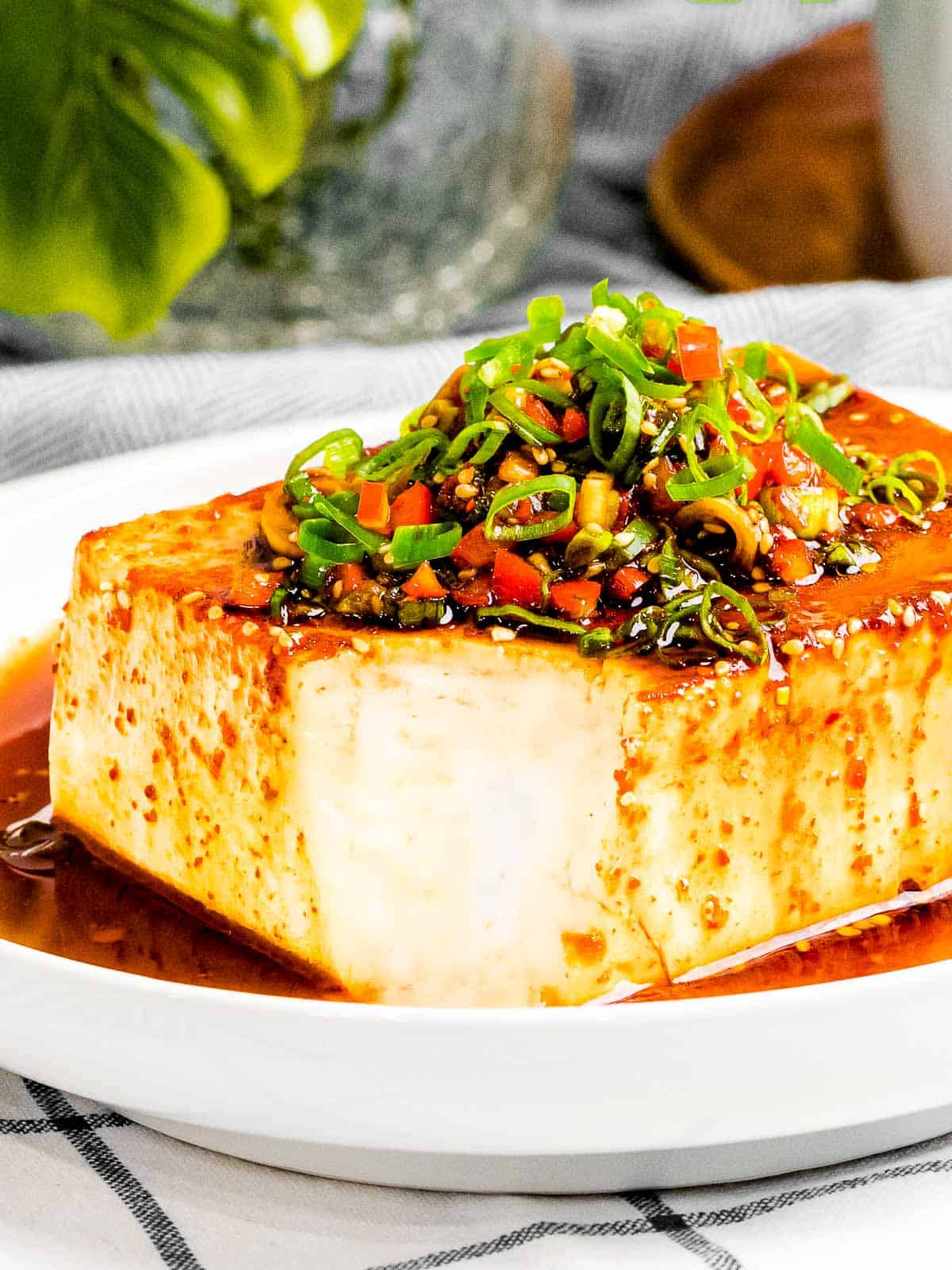 Easy silken tofu with vegan Korean soy sauce with green onions, red peppers, and sesame seeds.