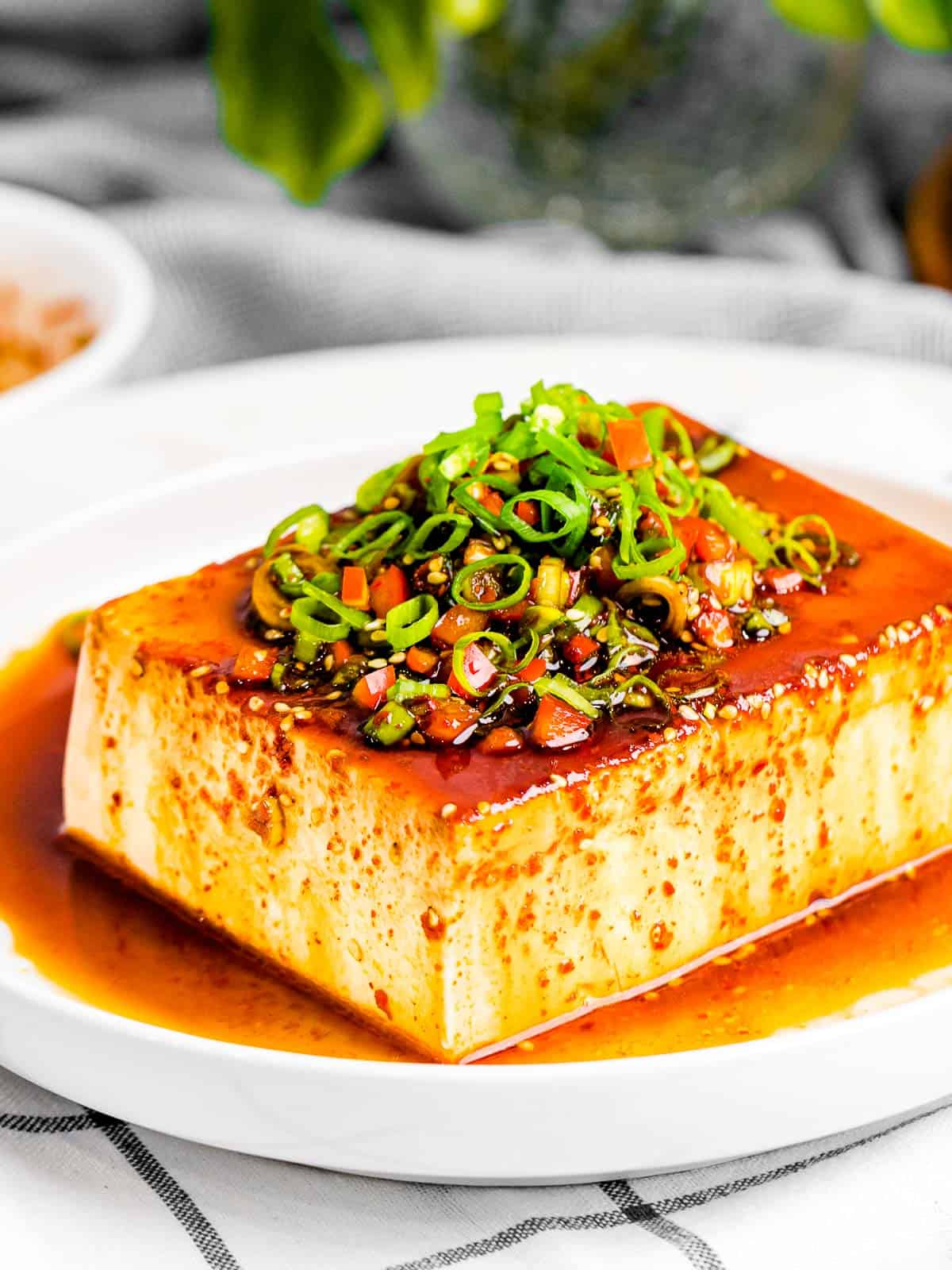 Silken tofu with easy Asian soy sauce made with green onions, red pepper flakes, and soy sauce in a white bowl.