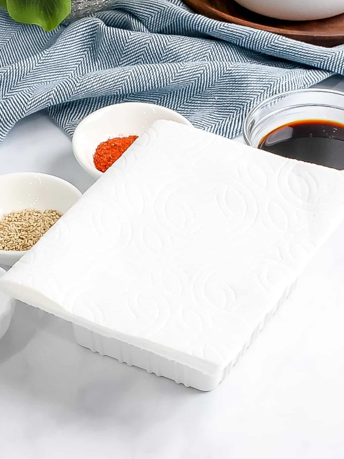 Paper towel laid on top of silken tofu container.