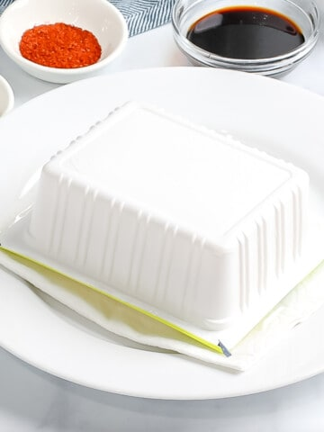 Silken tofu draining upside down on a paper towel.