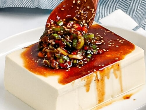 Soy sauce and green onions being poured over silken tofu with a wooden spoon.