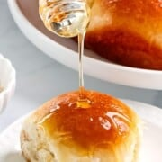 Sweet brioche dinner rolls drizzled with honey.