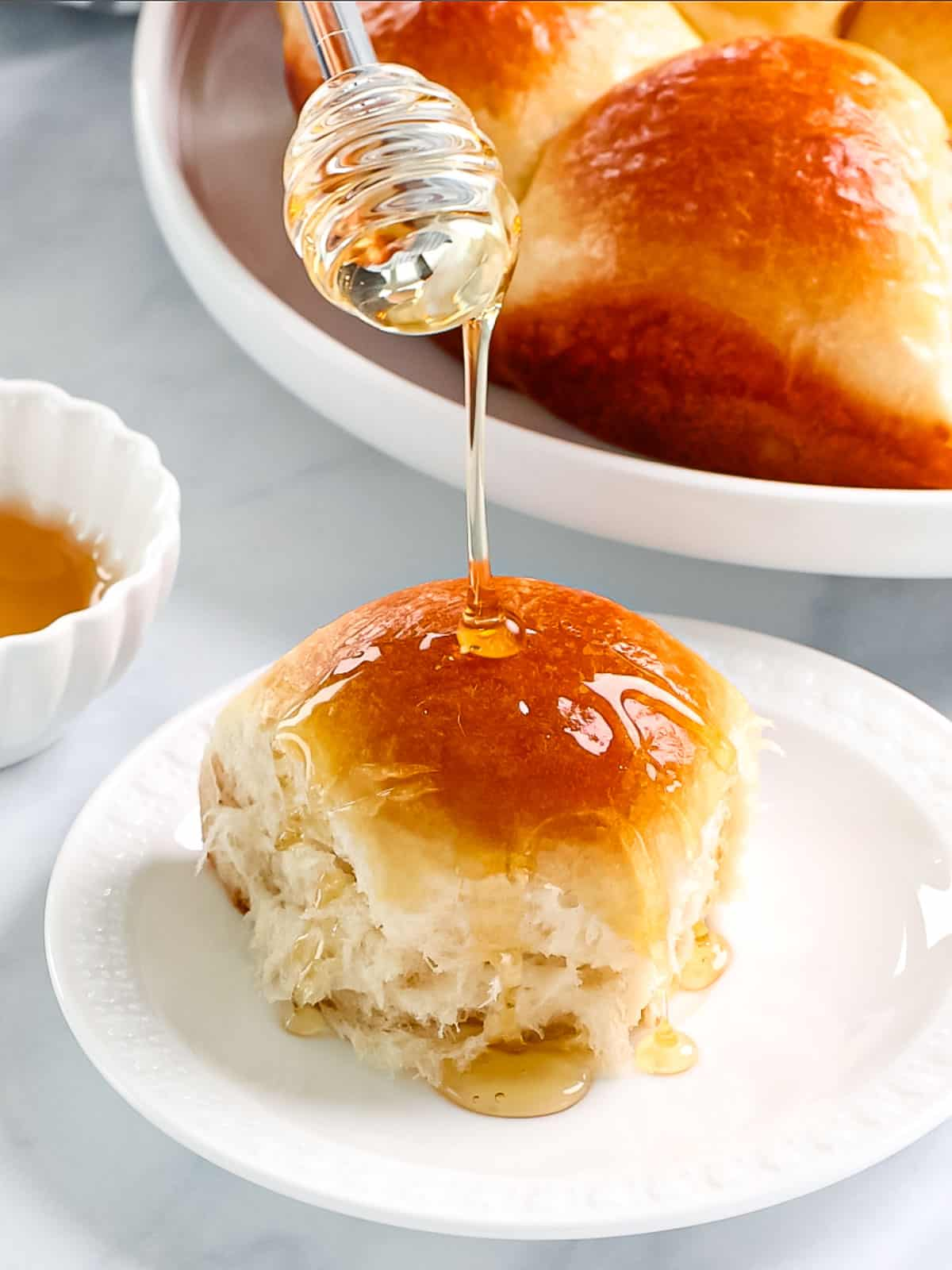 Buttery brioche rolls being drizzled with honey.