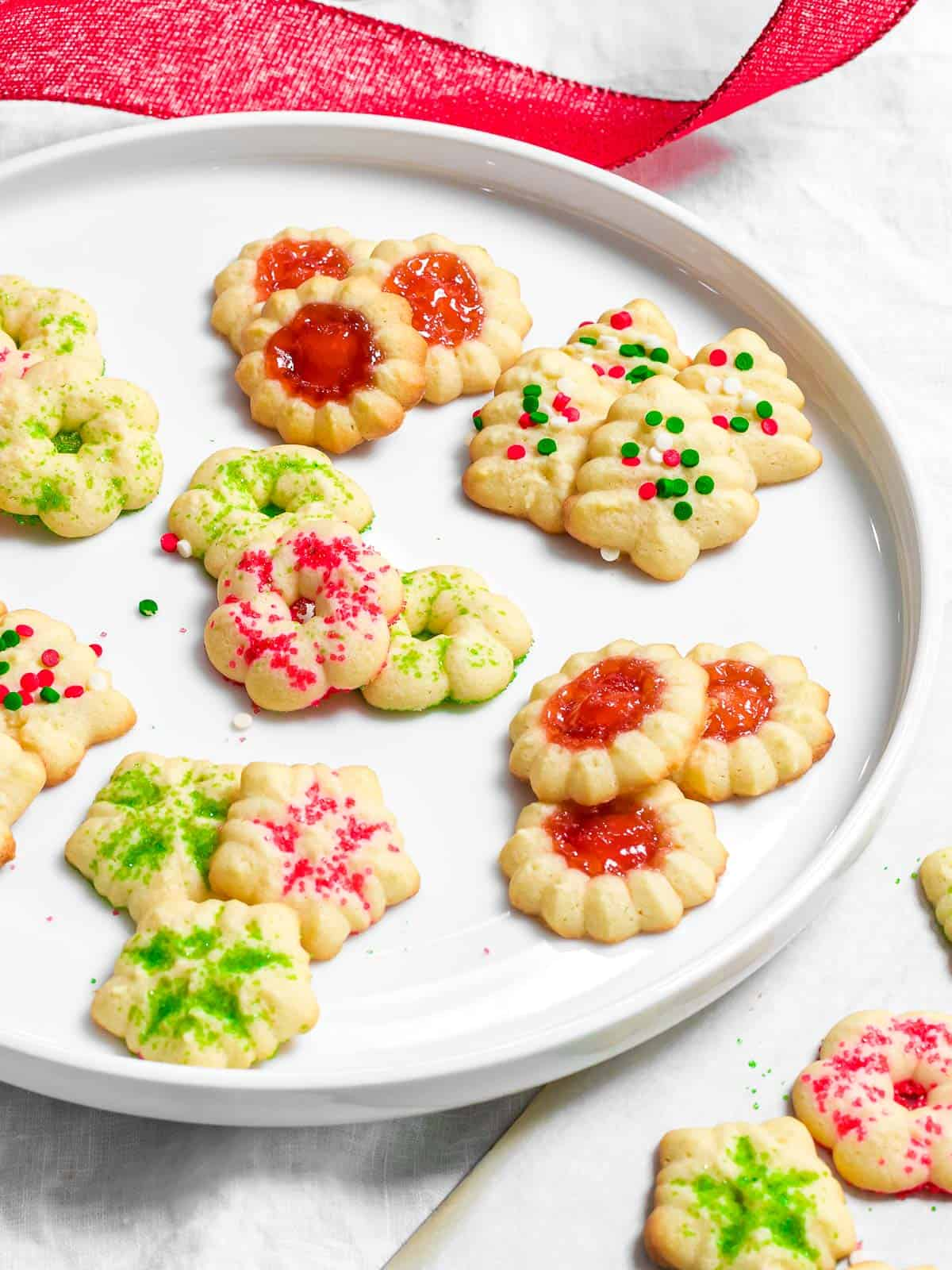 Easy Christmas spritz cookies in the shapes of trees, snowflakes, and wreaths decorated with red and green holiday sprinkles on a plate.