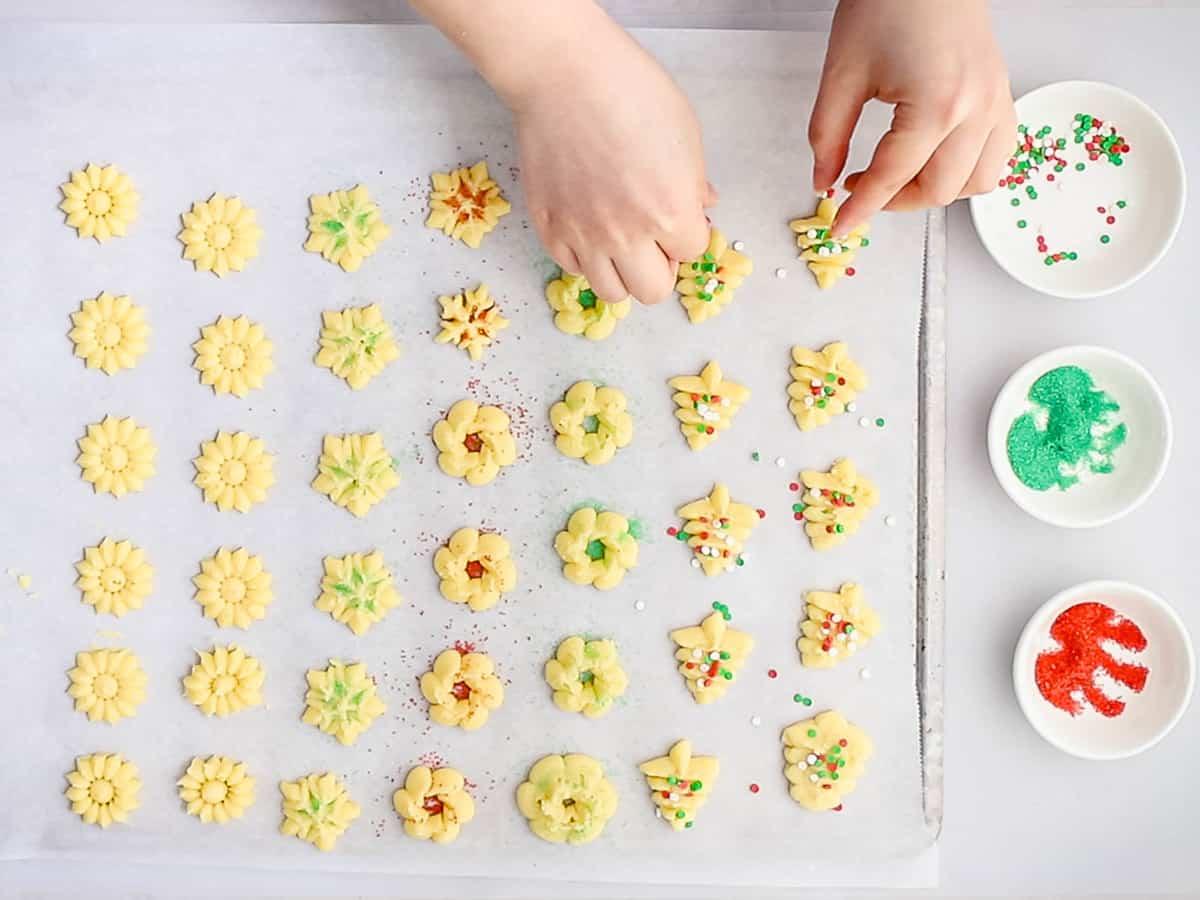 Adding Christmas sprinkles to Christmas spritz cookies.